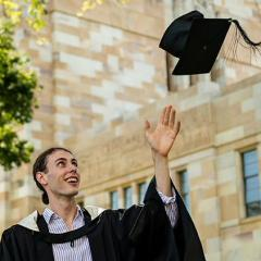 Kailin Graham in his graduation gown in UQ's Great Court