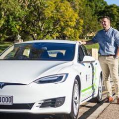 Jake Whitehead beside electric vehicle